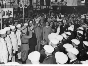 1936 06 - Dworzec Berlin Powitanie polskiej ekipy olimpijczyków. W jasnym garniturze płk Kazimierz Glabisz. Za nim (w rogatywce) mjr W Steblik z żoną, obok niej Halina Szymańska (w białym kapeluszu) (zbiory NAC)